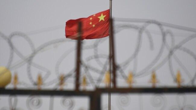 资料照:中国国旗在新疆喀什南部地区一处建筑物的围栏铁丝网后飘扬。(2019年6月4日)