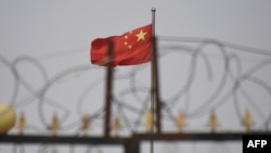 FILE - The Chinese flag flutters behind razor wire at a housing compound in Yangisar, south of Kashgar, in China's western Xinjiang region, June 4, 2019.