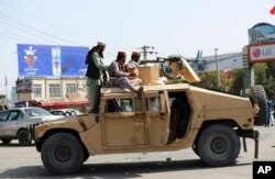 Taliban fighters stand guard in front of the Hamid Karzai International Airport, in Kabul, Afghanistan, Aug. 16, 2021.