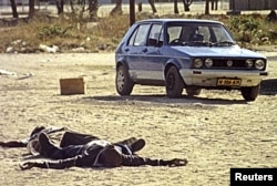 FILE - Two bodies of rebel insurgents lie in a street after sporadic gunfire in the Caprivi strip, Namibia, Aug. 3, 1999.