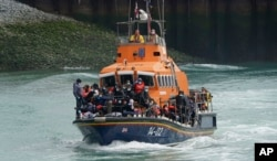 A group of people thought to be migrants are brought in to Dover onboard a lifeboat following a small boat incident in the Channel, in Kent, England, July 4, 2021.
