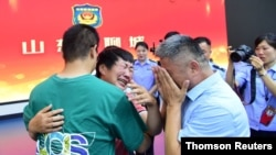 Guo Gangtang and his wife reunite with their son Guo Xinzhen, who was abducted 24 years ago, in Liaocheng