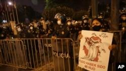 """Una mujer sostiene un cartel que dice en español """"Pudo haber sido mi hijo"""" y se une a una protesta contra la impunidad y por una reforma constitucional, en Lima, Perú, el martes 17 de noviembre de 2020."""