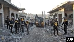 Anggota Pertahanan Sipil Suriah, atau dikenal Helm Putih, membawa ekskavator di jalan yang dipenuhi puing-puing bangunan menyusul serangan udara di Desa Balyun di Provinsi Idlib, 7 Desember 2019.