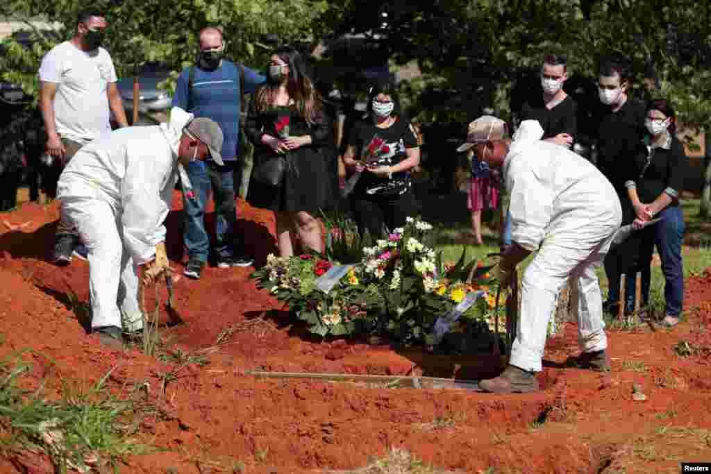 En Sao Paulo, Brasil, familiares de un hombre que falleció por COVID-19 asisten a su velorio. Trabajadores con trajes protectores entierran el ataúd con el cuerpo en el cementerio de Vila Formosa.