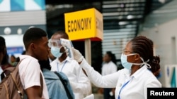 FILE PHOTO: A health worker checks the temperature of a traveller as part of the coronavirus screening procedure at the Kotoka International Airport in Accra, Ghana January 30, 2020. REUTERS/Francis Kokoroko/File Photo