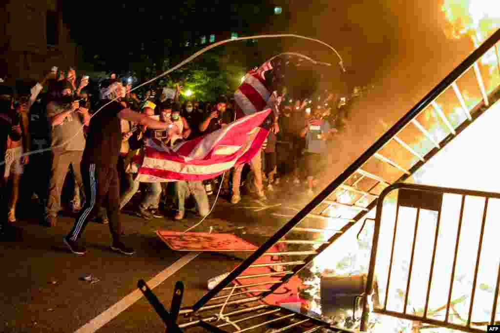 Protesters throw a US flag into a fire during a demonstration outside the White House over the death of George Floyd at the hands of Minneapolis Police in Washington, DC, on May 31, 2020.
