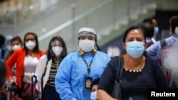 Viajeros con mascarillas protectoras durante la reapertura del Aeropuerto Internacional Mons. Oscar Arnulfo Romero de El Salvador el 19 de septiembre de 2020.