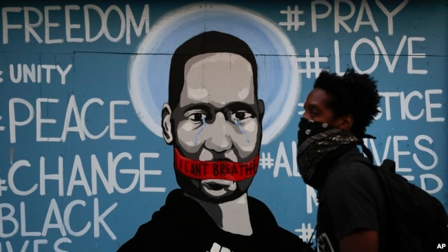 A man with a face covering walks past a mural depicting George Floyd during a protest in Los Angeles, May 31, 2020.