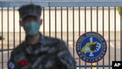 In this Feb. 21, 2020, photo, a South Korean marine wearing a mask stands in front of the Navy Base after a soldier of the unit was confirmed to have been infected with the coronavirus on Jeju Island, South Korea. The U.S. and South Korean…