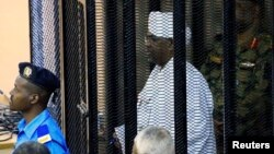 FILE - Sudan's former president Omar Hassan al-Bashir stands guarded inside a cage at the courthouse where he is facing corruption charges, in Khartoum, Sudan, Aug. 19, 2019.