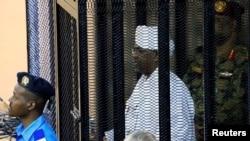 Rais wa zamani wa Sudan Omar Hassan al-Bashir akiwa mahakamani kwenye kizuizi cha vyuma akikabiliwa na mashtaka ya ufisadi, Khartoum, Sudan, Aug. 19, 2019.