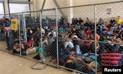 FILE - An overcrowded fenced area holding families at a Border Patrol station is seen in a still image from video in McAllen, Texas, June 10, 2019.