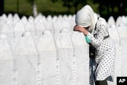 A woman leans on a grave stone in Potocari, near Srebrenica, Bosnia, July 11, 2020.