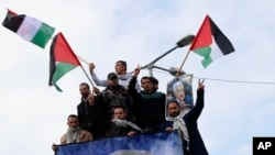 Protestors wave Palestinian flags during a rally supporting Palestinian President Mahmoud Abbas, shown in banner, and against the Mideast plan announced by U.S. President Donald Trump, at the Unknown Soldier Square in Gaza City, Feb. 11, 2020.