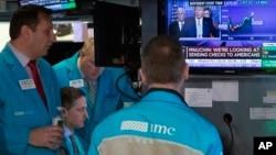 2020年3月17日,纽约证券交易所交易员在听特朗普总统在白宫的电视新闻发布会。